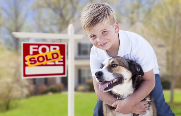 Happy Young Boy and His Dog in Front of Sold For Sale Real Estat